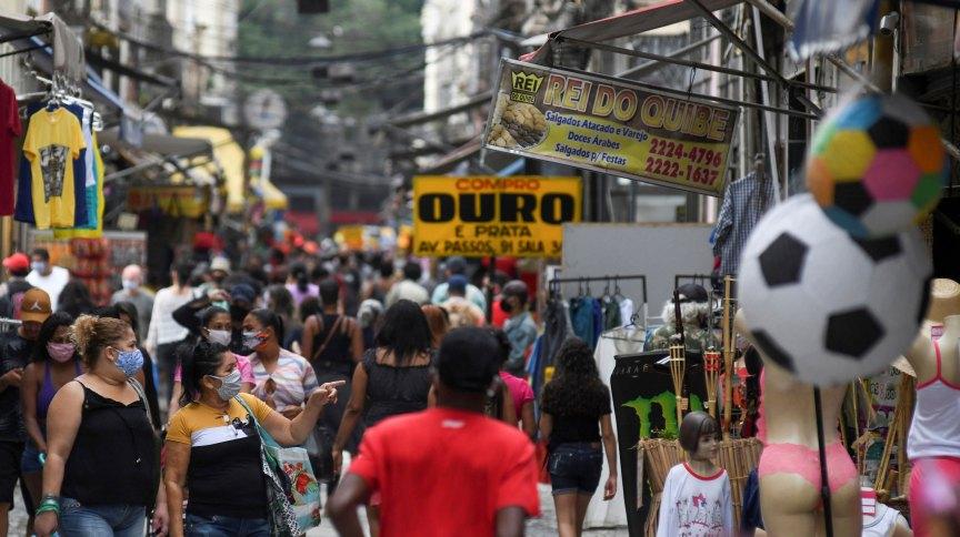 Pessoas caminham de máscara em rua comercial do Rio de Janeiro durante pandemia da Covid-19
