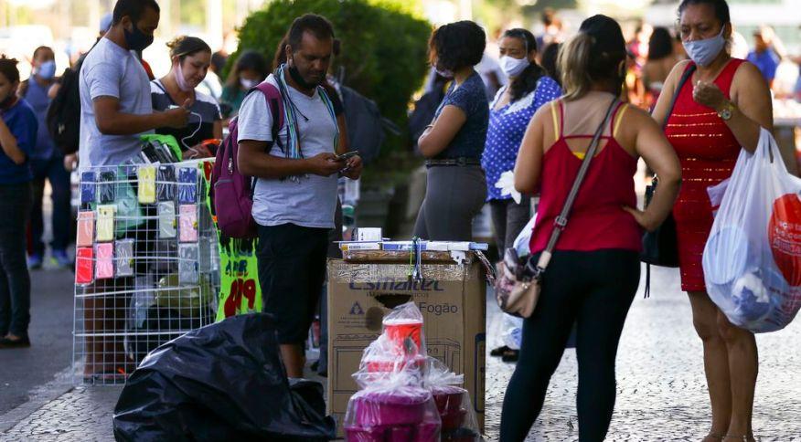 Pessoas com e sem máscara em comércio de rua em Brasília