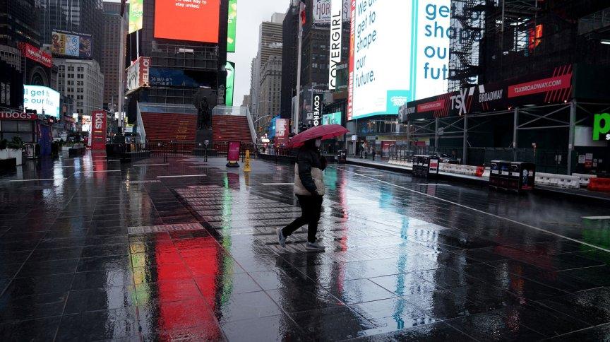 Pedestre caminha na Times Square praticamente vazia, em Nova York, em meio à pandemia do coronavírus