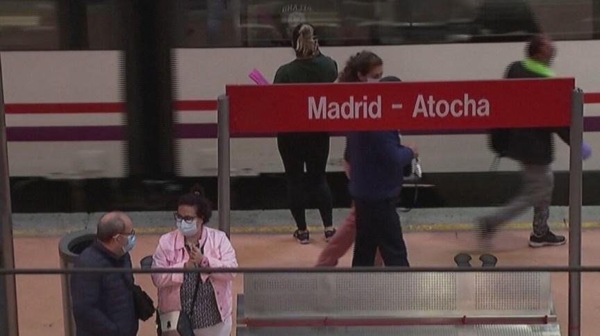 Pessoas usam máscara e álcool gel em rua na Espanha