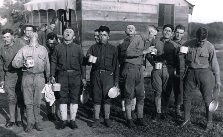 Em setembro de 1918, durante a pandemia de gripe espanhola, homens fazem gargarejo com água salgada após um dia de trabalho em Camp Dix, em Nova Jersey. Essa foi uma das medidas preventivas contra a pandemia, que se espalhou para os acampamentos