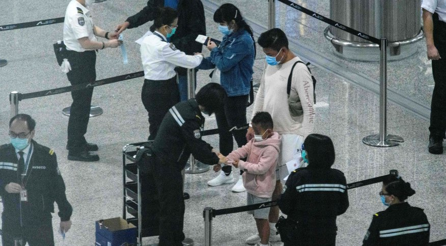 Oficiais colocam pulseiras de monitoramento em viajantes chegando à Hong Kong (20.mar.2020)