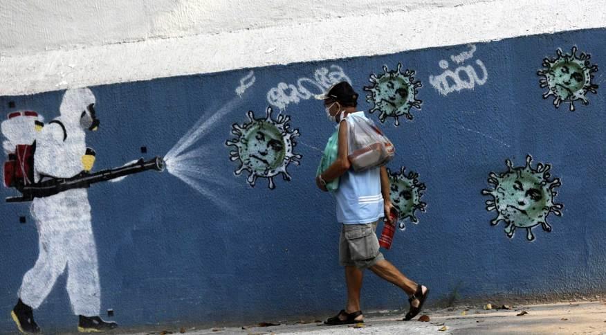 Homem passa por grafite no Rio de Janeiro durante pandemia da Covid-19
