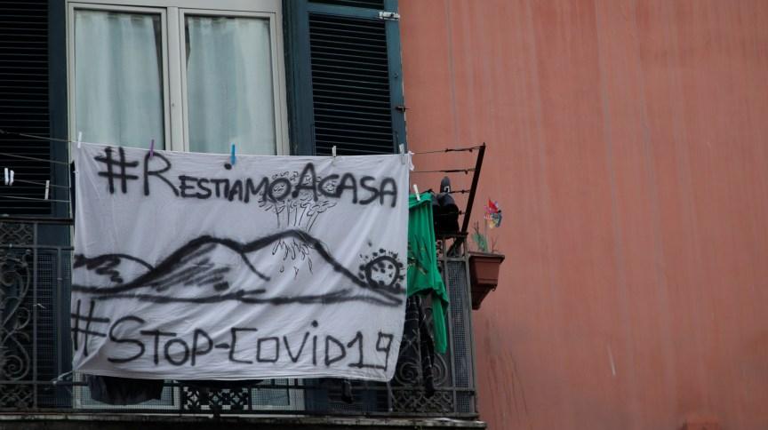 Cartaz em balcão de casa em Nápoles, na Itália, pede que pessoas fiquem em casa para impedir avanço do COVID-19
