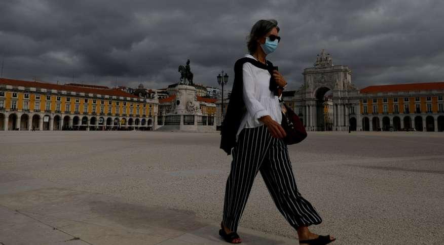 Mulher de máscara caminha na Praça do Comércio, em Lisboa
