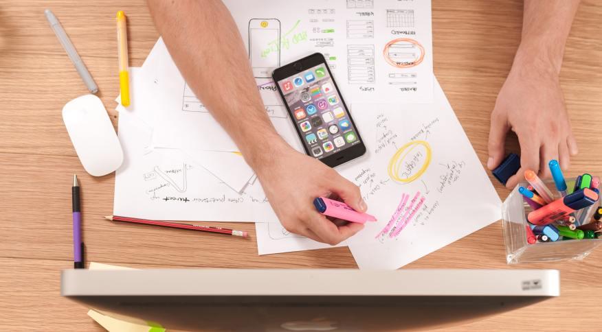 Jovem faz anotações durante o curso online; conheça instituições que oferecem cursos gratuitos de finanças