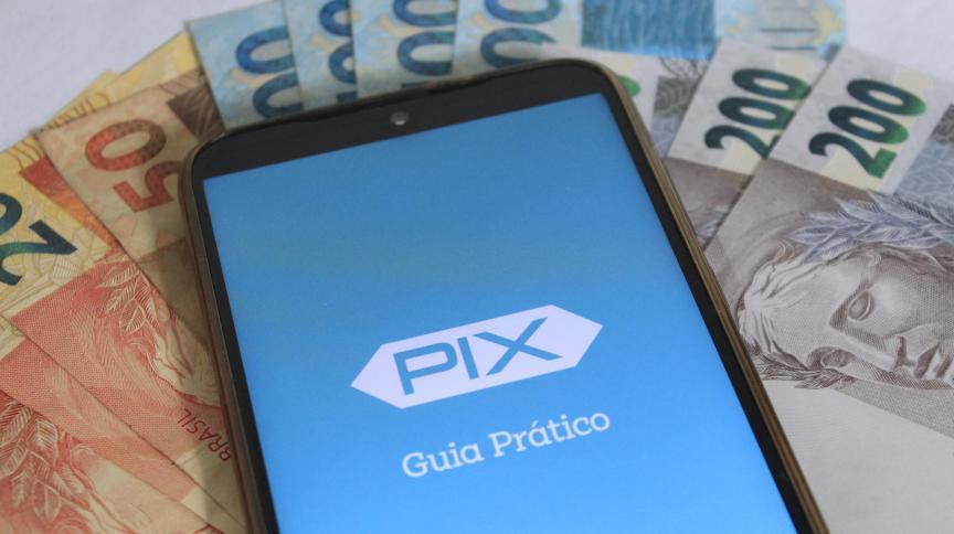 Notas de real ao lado smartphone: Pix entrou em vigor nesta segunda-feira (16)