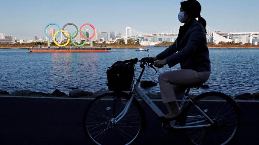 Ciclista passa pelos anéis olímpicos em Tóquio