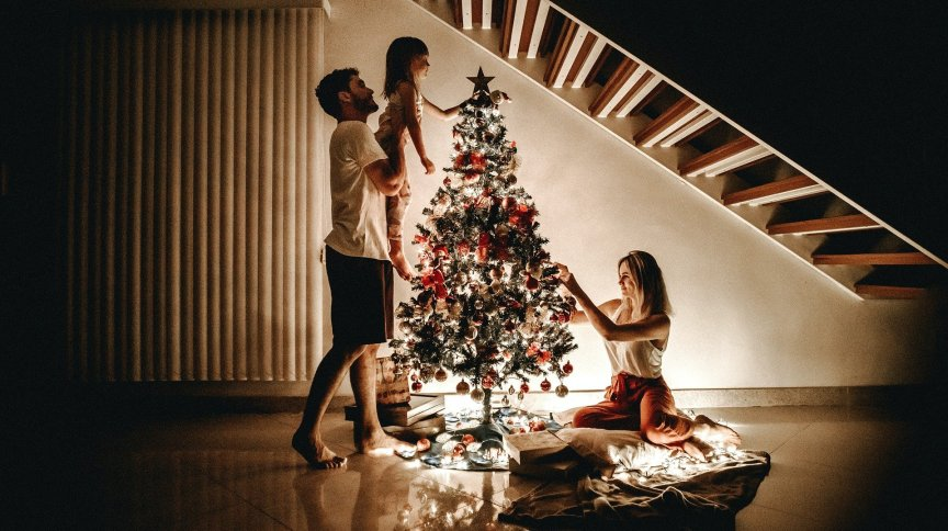 Família reunida em torno de árvore de Natal