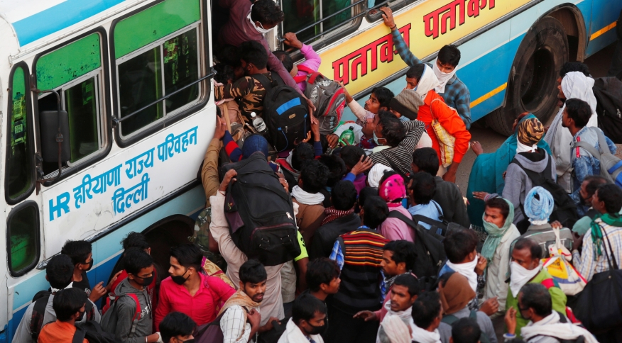 Trabalhadores migrantes tentam embarcar em ônibus para retornar ao interior do país e fugir da COVID-19