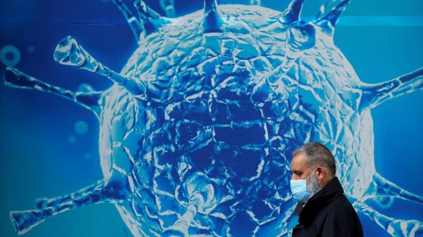 Homem passa por ilustração de vírus em Oldham, Reino Unido (Arquivo: 03/08/2020)