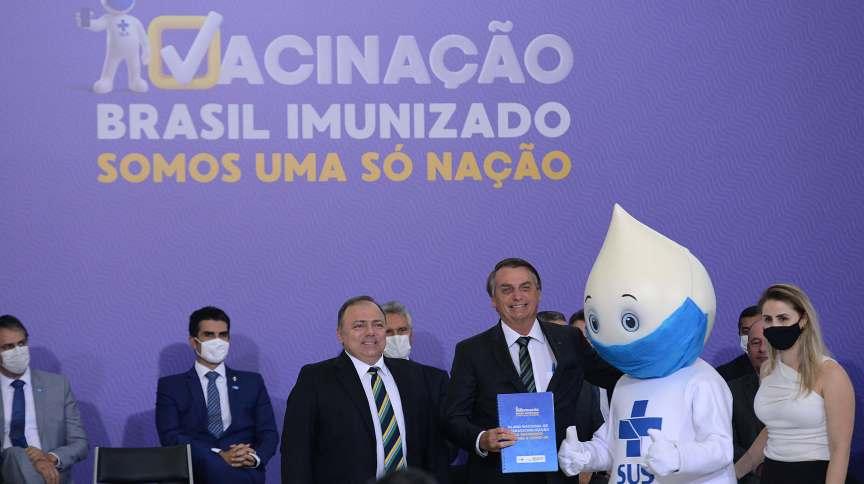 O presidente da República, Jair Bolsonaro (c) abraça o mascote Zè Gotinha no lançamento do plano nacional de imunização contra a covid-19 (16.dez.2020)