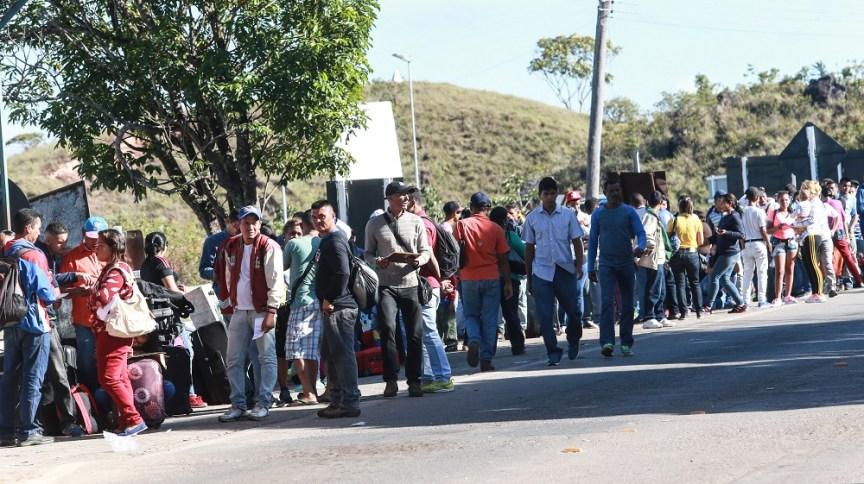 Imigrantes venezuelanos cruzam a pé a fronteira entre Venezuela e Brasil, próximo ao município de Pacaraima, em Roraima