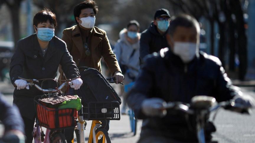 Pessoas usam máscaras para andar de bicicleta em Pequim em meio ao surto de COVID-19