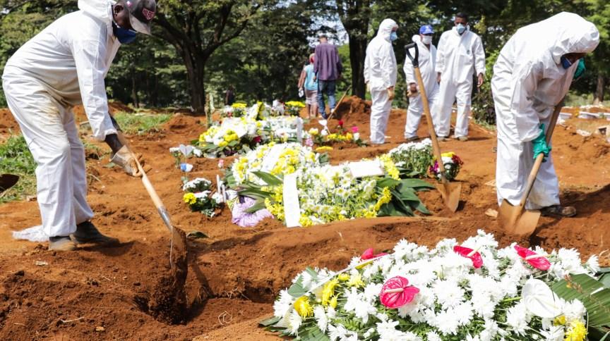 Coveiros usam roupas de proteção em enterros no cemitério da Vila Formosa, em São Paulo