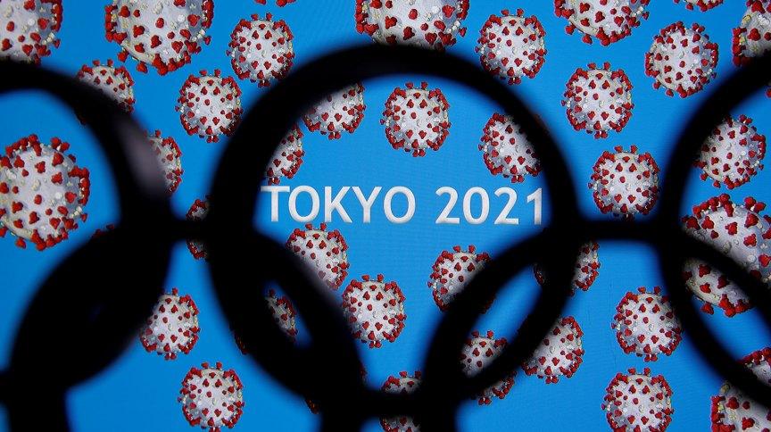 Arcos olímpicos na frente de painel anunciando adiamento dos Jogos de Tóquio para 2021