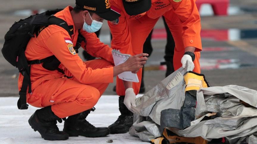 Equipe de resgate analisa destroços encontrados no local da queda da aeronave, no Mar de Java