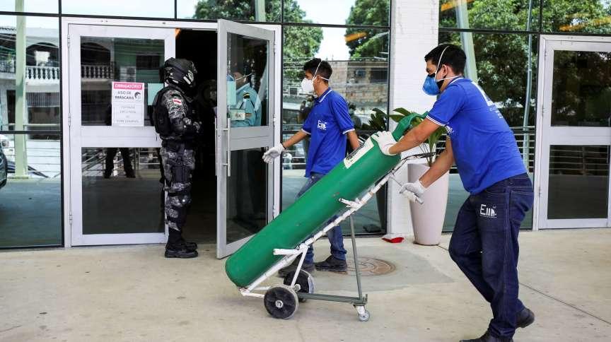 Trabalhadores chegam a hospital em Manaus, no Amazonas, com cilindro de oxigênio