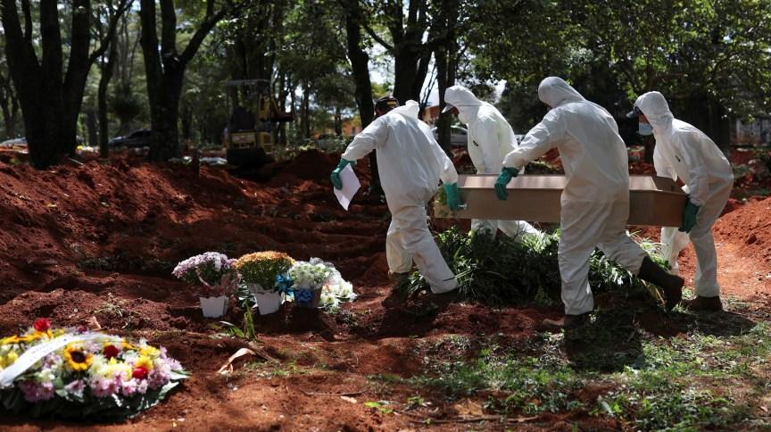 Coveiros usando trajes de proteção carregam caixão no cemitério de Vila Formosa, em São Paulo