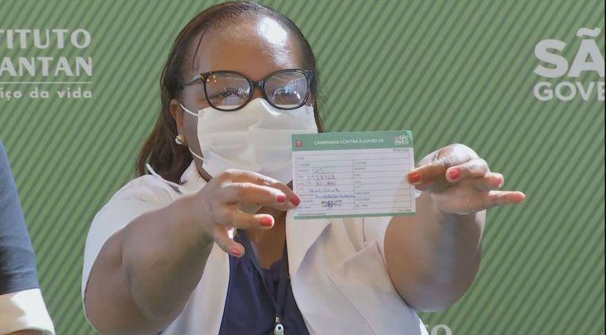 Primeira brasileira vacinada no Brasil exibe seu cartão de vacinação (17 jan 2021)