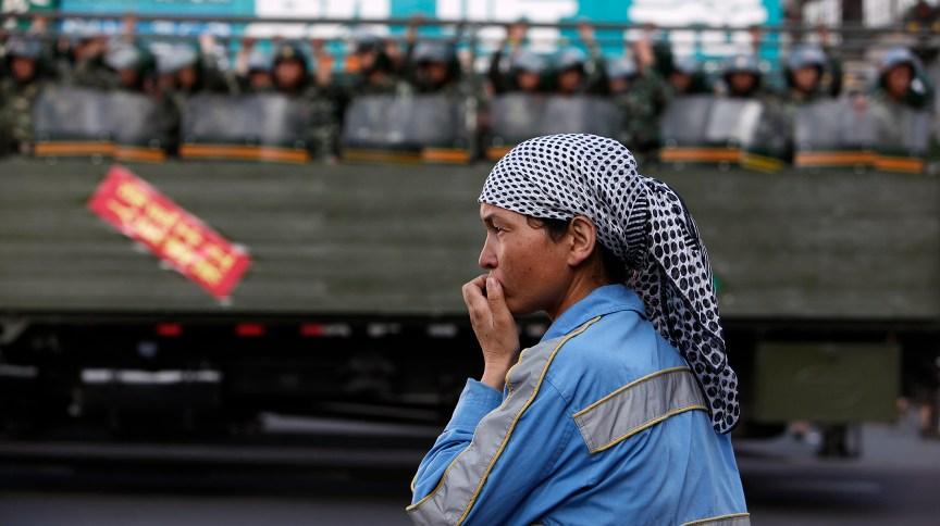 Mulher uigure na beira da estrada enquanto polícia paramilitar chinesa passa dentro de caminhão em rua de Urumqi, na região de Xinjiang, na China