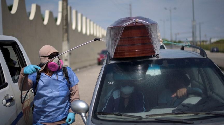 Funcionário do governo equatoriano passa desinfetante em carro carregando corpo de vítima do coronavírus em Guayaquil