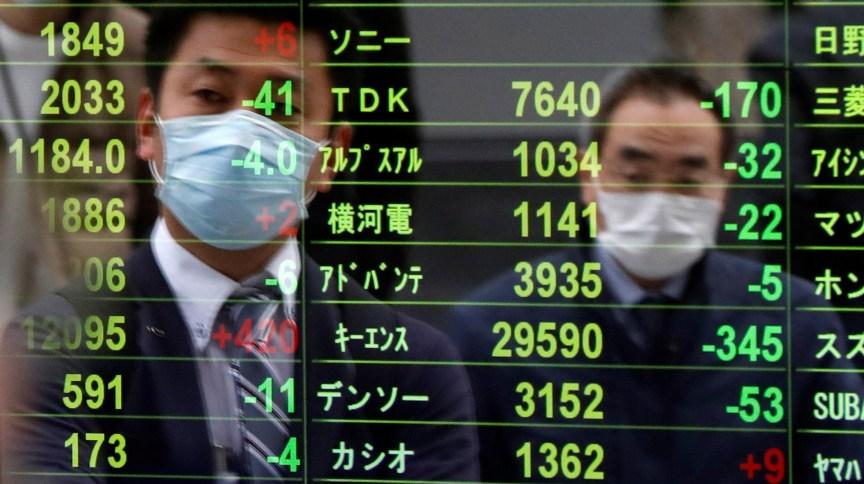 Homens usam máscaras na Bolsa de Tóquio