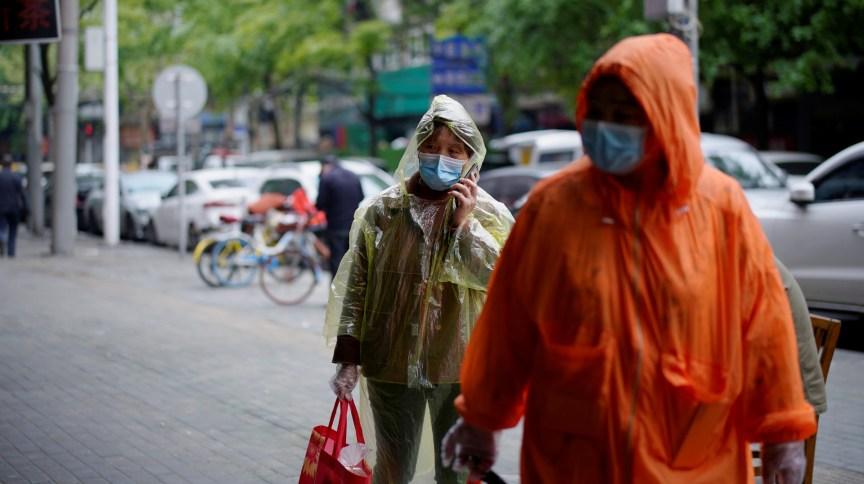 Pessoas com máscaras de proteção caminham em rua de Wuhan, na China, primeiro epicentro da Covid-19