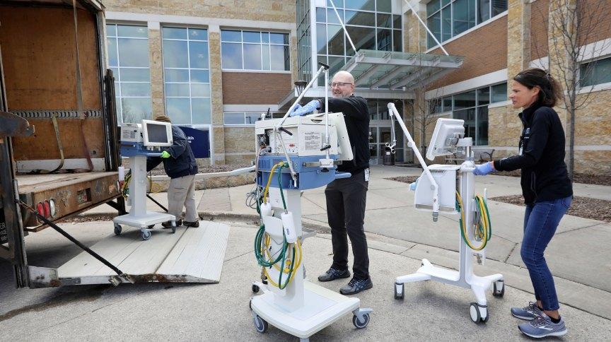 Funcionários da Madison Area Technical College transportam respiradores que a universidade disponibilizou para hospitais tratarem pacientes com COVID-19