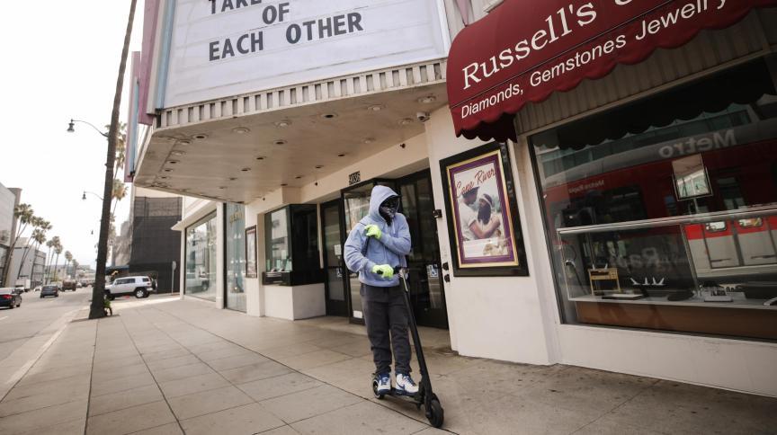 Homem usa bandana como máscara enquanto anda de patinete por rua de Beverly Hills, Califórnia
