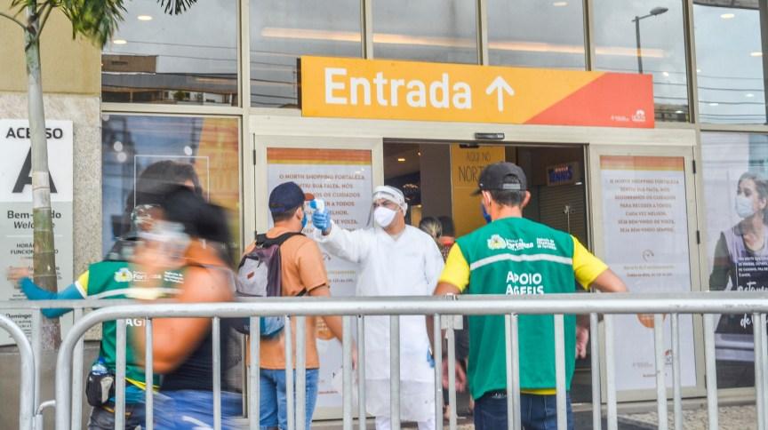 Funcionários da Agência de Fiscalização de Fortaleza monitoram temperatura na entrada de shopping na capital cearense