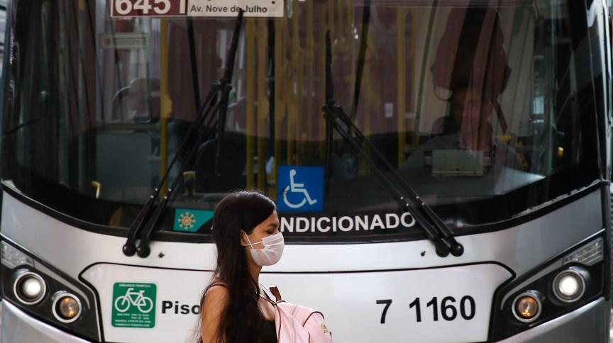 Transeunte usa máscara protetora em terminal de ônibus em São Paulo