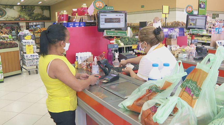 Consumir e caixa de supermercados usando máscaras de proteção contra a Covid-19