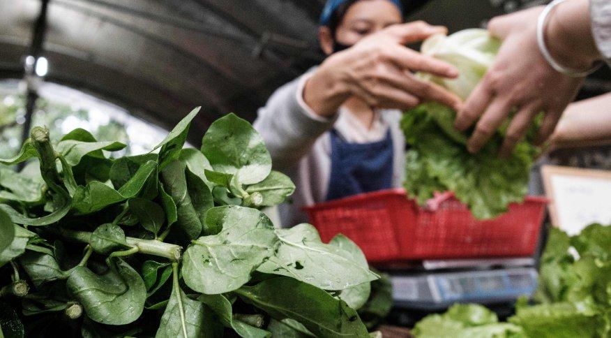 Mulher vestindo máscara vende legumes em uma fazenda comunitária em Hong Kong (18.mar.2020)