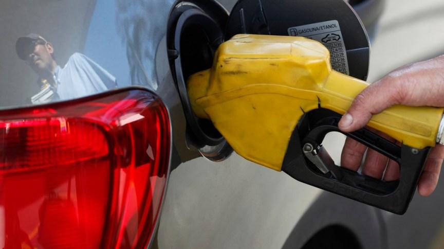 Funcionário de posto de gasolina abastece carro em São Paulo