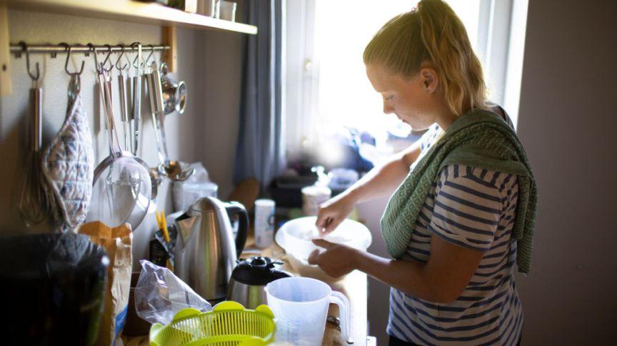 Mulher prepara refeição na cozinha na Holanda; trabalho doméstico