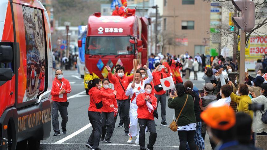 O cantor e compositor Hiroguchi Takao carrega a tocha olímpica pelas ruas de Iwaki, em Fukushima no 1º dos 121 dias do revezamento.jpg