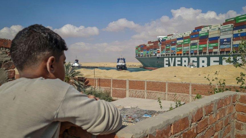 Garoto observa rebocadores tentarem desencalhar o navio Ever Given no canal de Suez