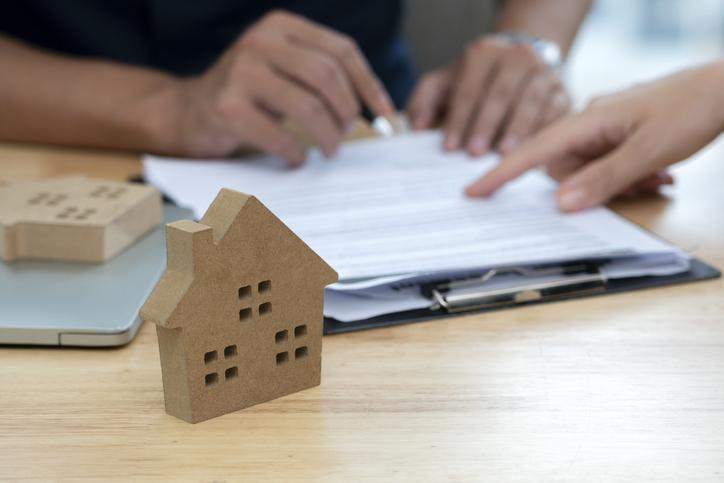 Pessoas revisam contrato para compra de imóvel