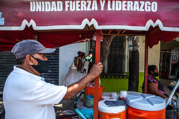Vendedor de comida usando máscara facial na rua de Pochutla, México. Páis é a segunda potência econômica da América Latina