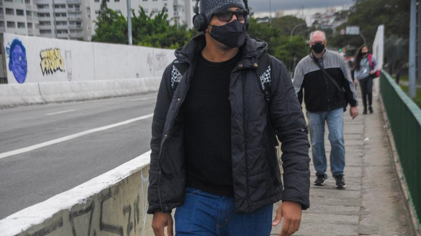 Pedestres se protegem do frio na cidade de São Paulo