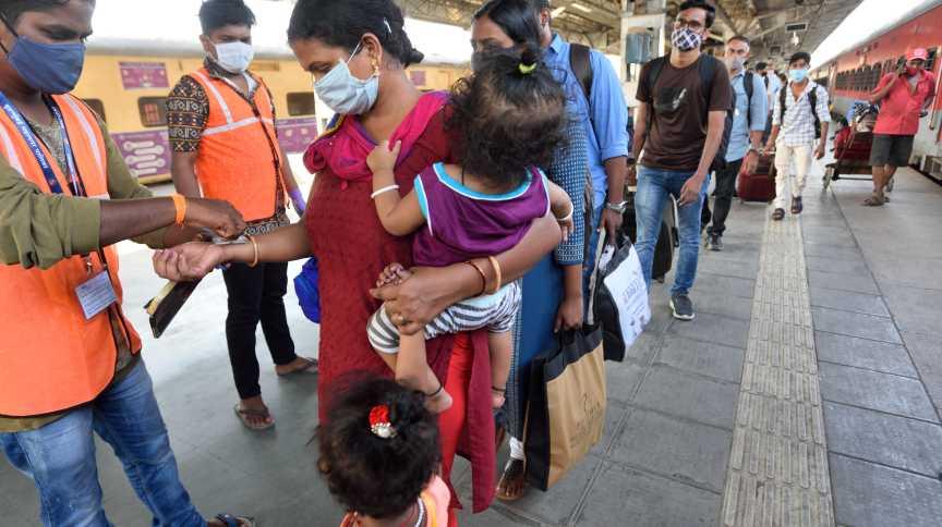 Funcionários de saúde marcam com carimbo de quarentena viajantes de Kerala que chegam em Mumbai, na Índia