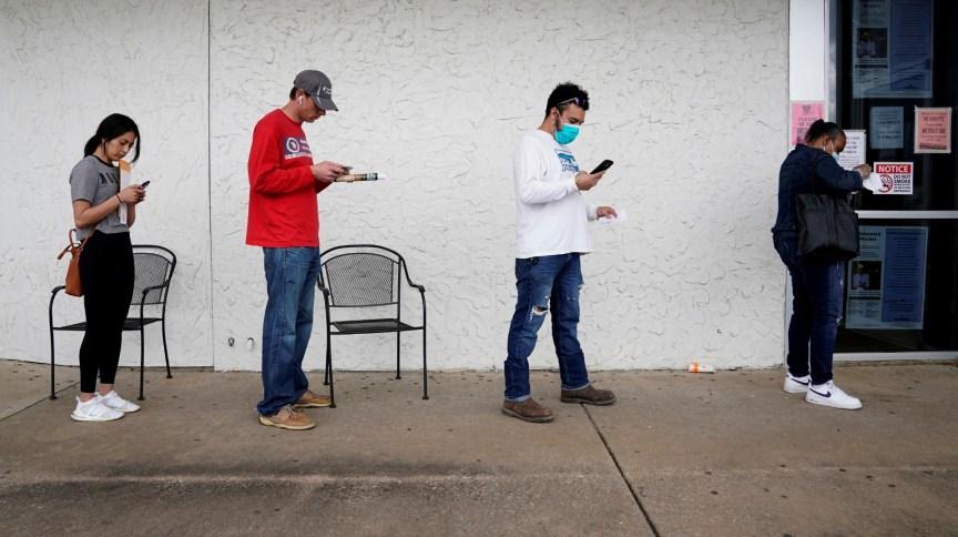 Pessoas desempregadas aguardam em fila para preencher formulário de vaga no Arkansas, EUA
