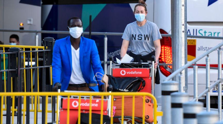 Passageiros usando máscaras chegam ao Aeroporto Internacional de Sydney