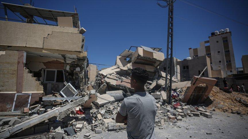 Palestinos inspecionam escombros de uma casa destruída por ataques aéreos israelenses em Khan Yunis, ao sul da Faixa de Gaza