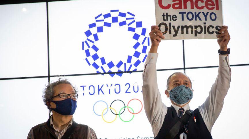 """Manifestante segura cartaz que diz """"Cancelem a Olimpíada de Tóquio"""" em inglês, durante protesto em Tóquio, em 17/05/2021"""