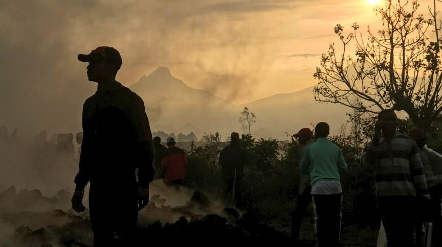 Moradores caminham perto de casas destruídas por lava de vulcão no arredores de Goma, na República Democrática do Congo