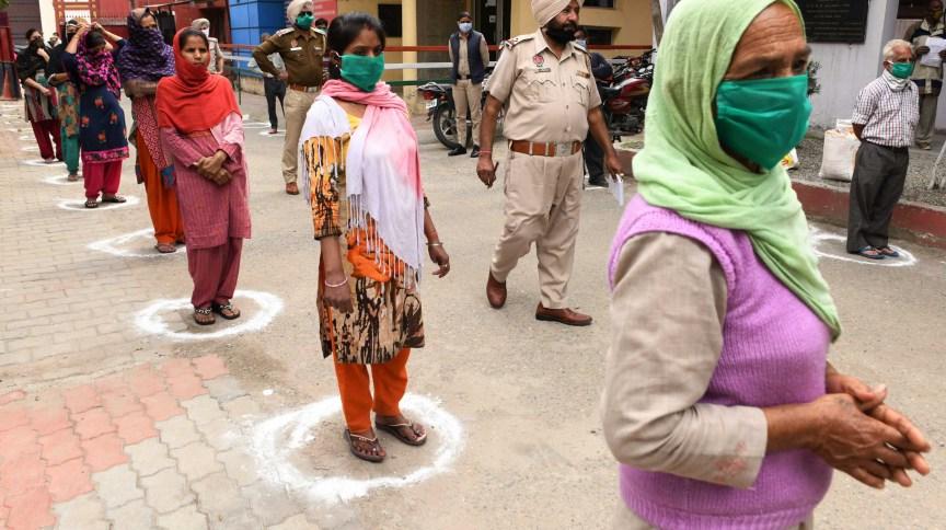 As pessoas mantêm a distância recomendada, enquanto esperam para receber mercadorias distribuídas por policiais durante a quarentena em Amritsar. Índia, 29 de abril de 2020.