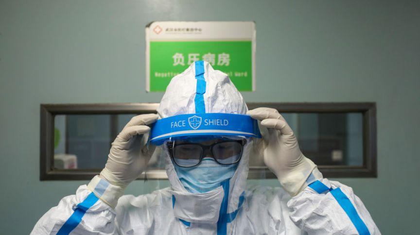 Médico se prepara para entrar na zona de isolamento da Covid-19 em Wuhan, em fevereiro de 2020
