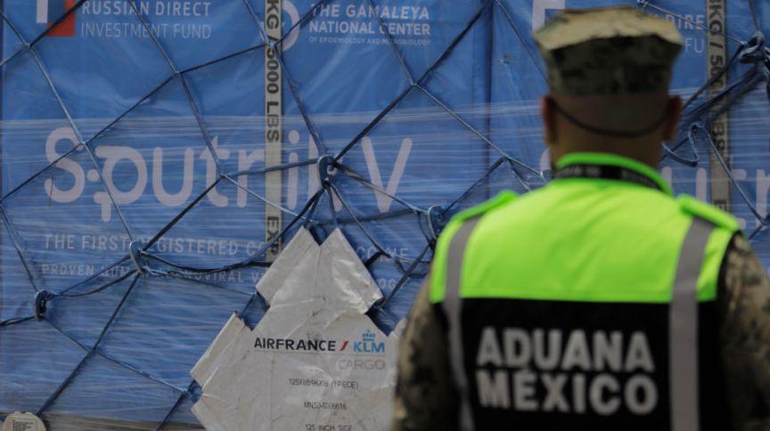 Guarda mexicano assiste à chegada de avião da Air France com um carregamento de 500 mil doses de Sputnik V, a vacina da Rússia: o mundo da imunização é interligado
